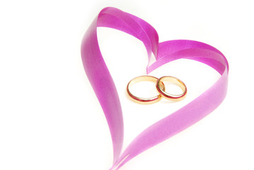 Close-up photo of the ribbon heart with wedding rings