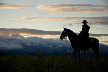 Cowboy silhouette against dawn sky
