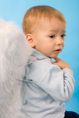 small serious boy dressed as Cupid on blue background