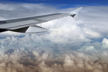 Airplane wing over majestic colorful tropical cloudscape.