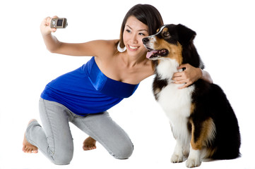 A young woman takes a photo with her pet dog