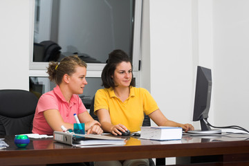 Two young women in office work on computer.  Business concept