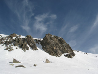 Snow covered high mountain rocks with blue sky in the background