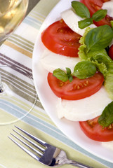 A fresh caprese salad with a glass of white wine