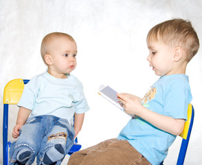 Kid reading book to brother. White window background