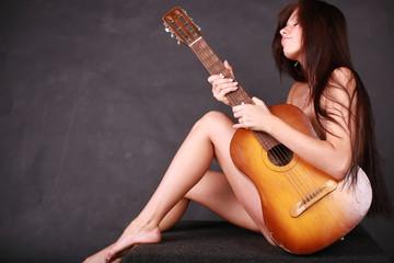 Beautiful girl sits and plays guitara