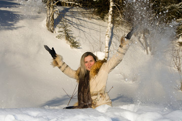 Young beautiful girl on the nature throwing snow.