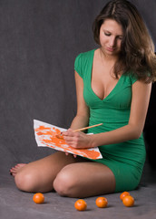 young girl in green dress painting orange picture