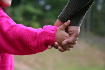 A mixed race mother and daughter holding hands