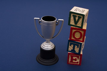 Trophy with vote alphabet blocks on a blue background
