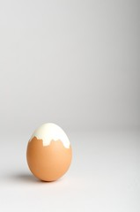 Partially peeled hard boiled egg on neutral background