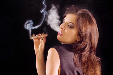 Young beautiful woman blowing smoke rings from cigar