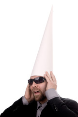 Man in a dunce  cap with sunglasses over a white background