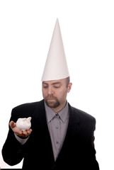 Man in a dunce cap with a piggybank over a white background