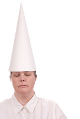 Woman in a dunce cap with eyes closed over a white background