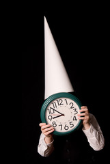 boy in a dunce cap holding a clock over a black background
