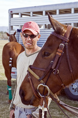 Groom with freshly outfitted polo horse