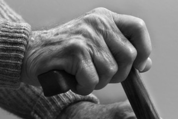 Hands that once tilled the earth now support frail body
