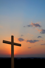 Wooden cross suring a colorful sunset