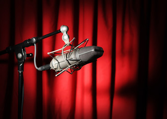 Wall Mural - Vintage microphone with spotlight over a red curtain