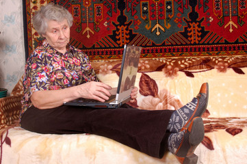 Seventy year old women with laptop on sofa