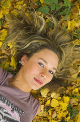 The beautiful girl lays in autumn leaves