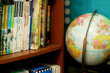 world globe and books on a shelf in a classroom