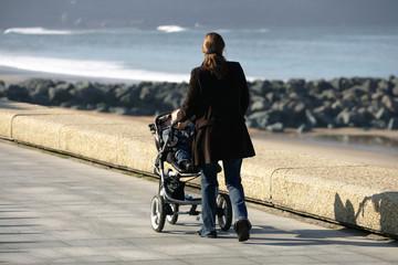 femme qui se promene avec son enfant dans une poussette