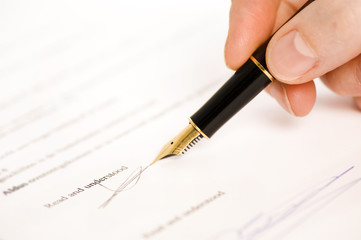 someone signing a document with a pen. text is blur.