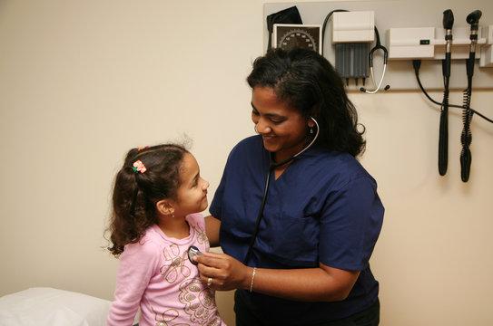 Hispanic nurse checks white child