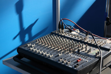 Mixing desk and shadow from microphone holders on a wall.