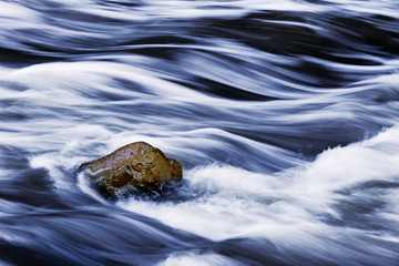 Water rushing by rock in river forming abstract appearance