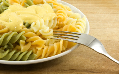Close-up of fork with coloured pasta with sauce