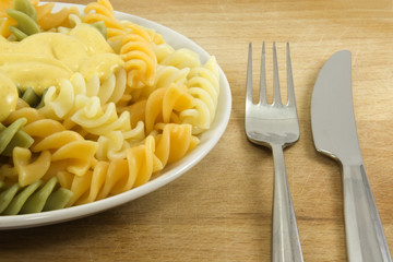 Close-up fork and knife with coloured pasta with sauce