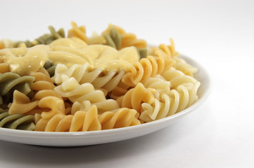 Close-up of coloured spiral macaroni on white background