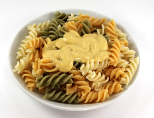 Dinner plate with coloured pasta and italian sauce on white