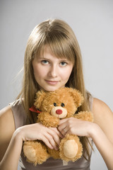 beautiful young girl holding a teddy bear toy