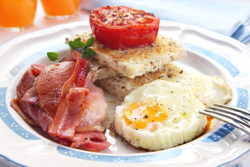 Breakfast of bacon and eggs, with grilled tomato