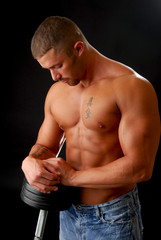 A muscular bodybuilder leaning on his weights