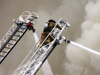 Fireman and hoses on ladders battling ferocious fire