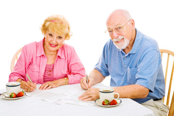 Senior couple filling out their absentee ballots for  election.