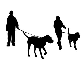 young couple walking dogs silhouette