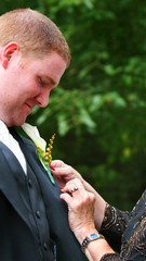 A boutonniere being pinned on the groom