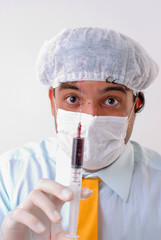Doctor using glove and holding a syringe .