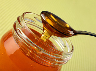 Honey in glass pot on green background