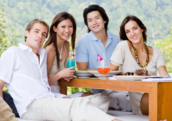 A group of four young adults sitting together to enjoy a meal