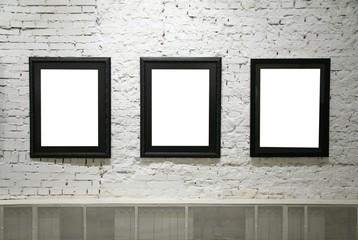 black frames on white brick wall