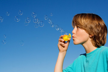 happy child playing blowing bubbles
