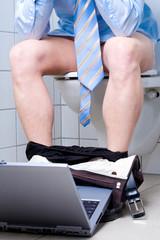 Geschäftsmann mit Laptop in Toilette