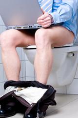 Mann mit blauem Hemd auf Toilette mit Laptop